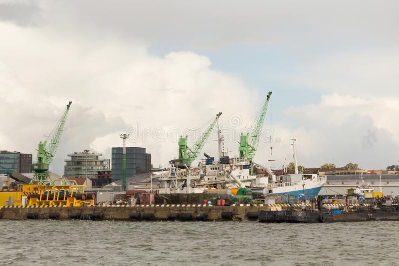 KLAIPEDA, LITUANIA - 22 DE SEPTIEMBRE DE 2018: Grúas y naves pesadas de horca del puerto en el embarcadero en el puerto marítimo  imágenes de archivo libres de regalías