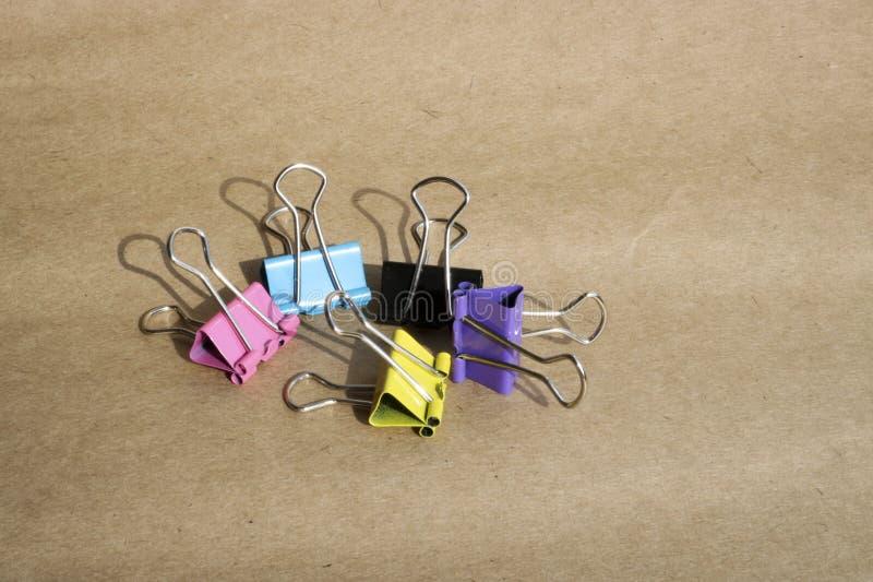 Klamerki dla papieru różni kolory na tle szorstki brązu Kraft papier materia?y zdjęcia royalty free