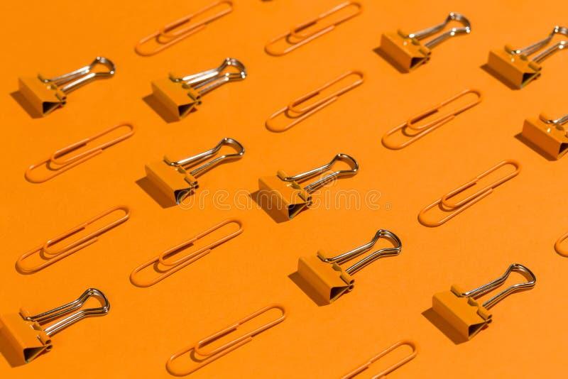 Klamerki i segregatory na pomarańczowym tle na pomarańczowy stacjonarnym, zdjęcie stock