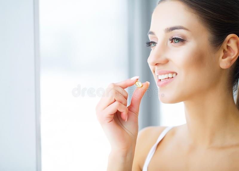 Klammern auf einem weißen Hintergrund Schöne junge Frau, die den Kaugummi, lächelnd isst stockfoto