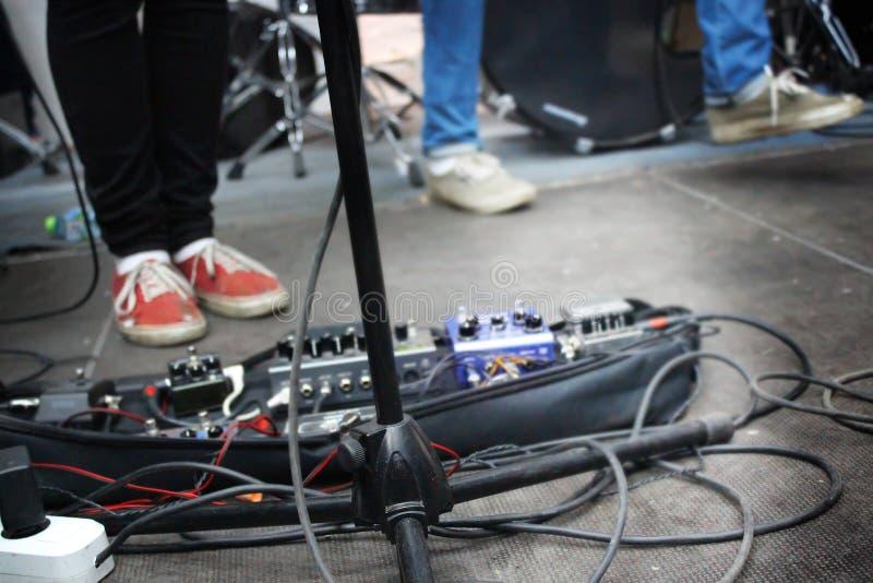 Klangeffekte des Gitarristen, solide Pedale des Gitarristen am Konzert lizenzfreie stockfotografie