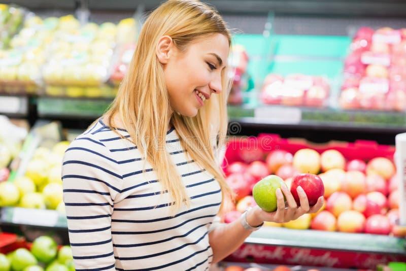 Klant bij de vruchten van de marktholding voorzijde van vruchten plank stock foto