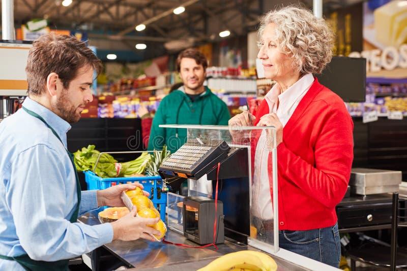 Klant bij supermarkt kijkt naar kassa's royalty-vrije stock afbeeldingen