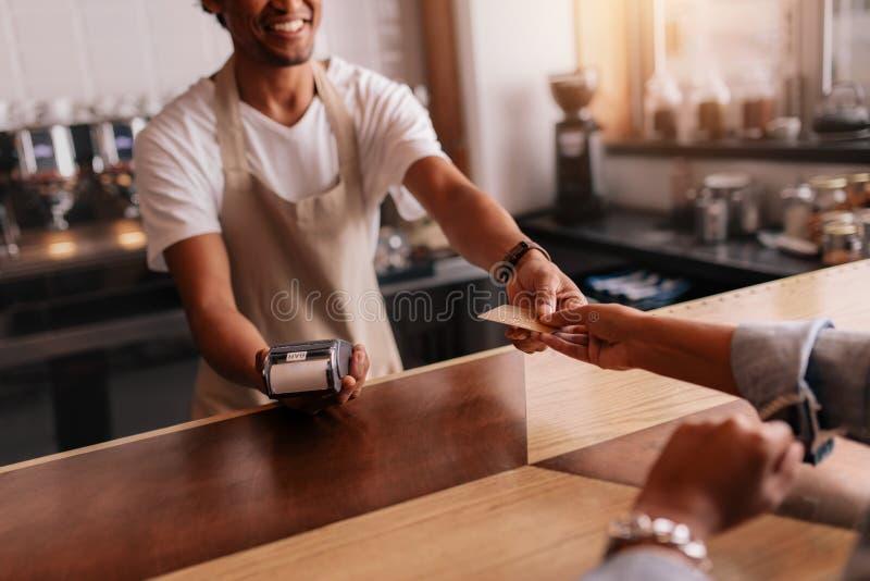 Klant die door creditcard bij koffiewinkel betalen royalty-vrije stock afbeelding