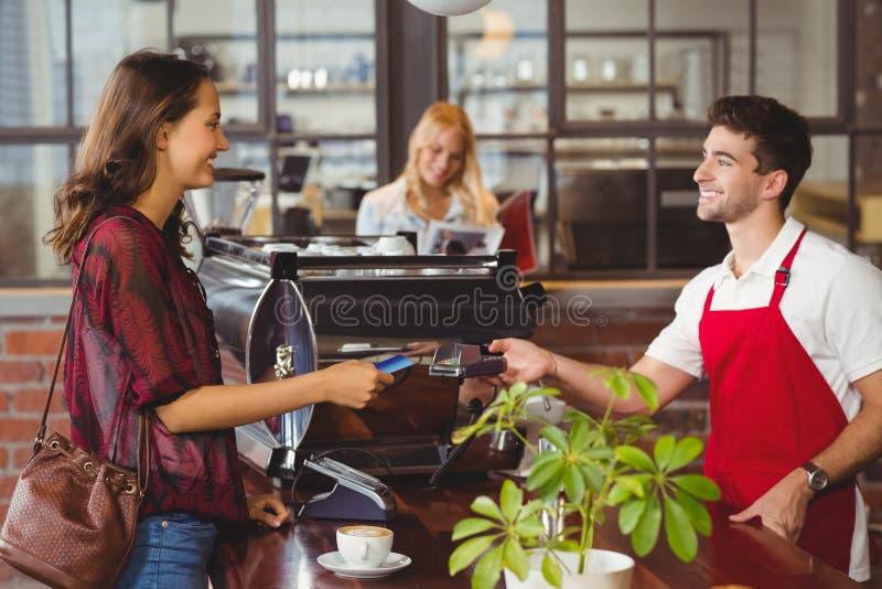 Klant die een creditcard overhandigen aan de kelner stock fotografie