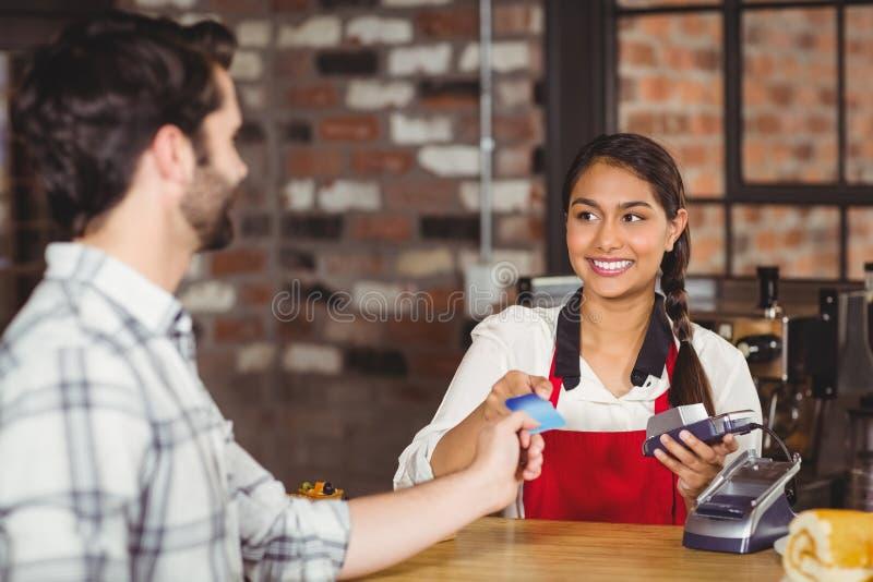 Klant die een creditcard overhandigen aan de serveerster royalty-vrije stock afbeeldingen