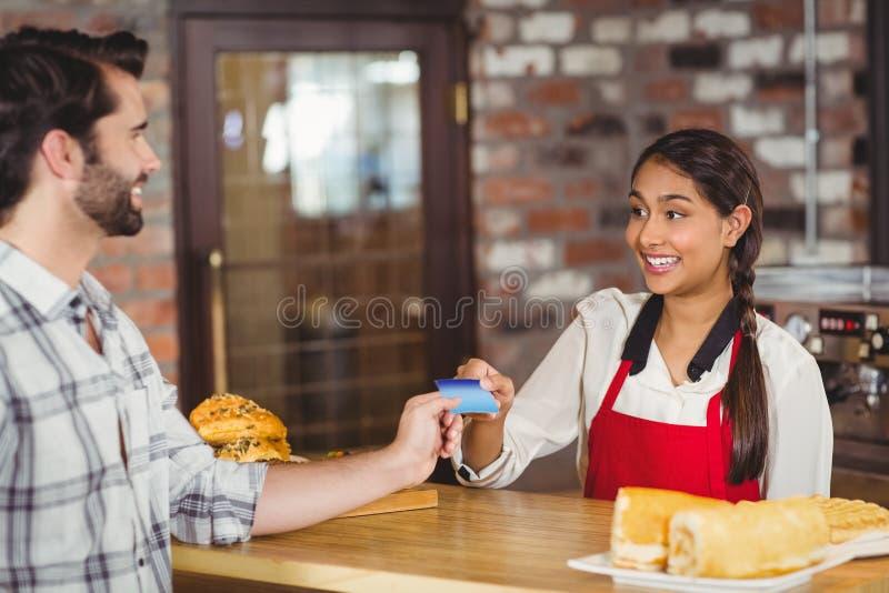 Klant die een creditcard overhandigen aan de serveerster stock foto