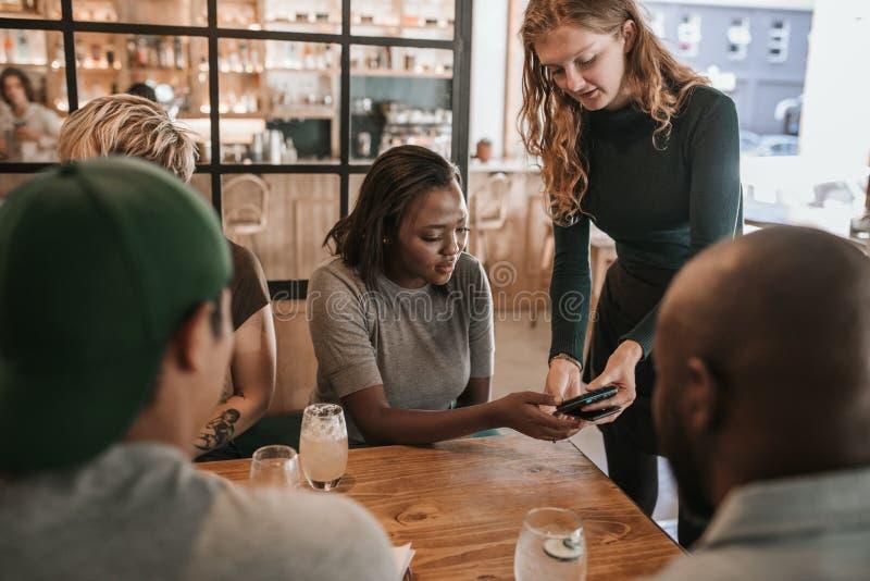 Klant die een restaurantrekening met haar smartphone betalen royalty-vrije stock fotografie