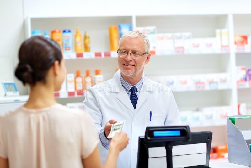 Klant die geld geven aan apotheker bij drogisterij stock foto