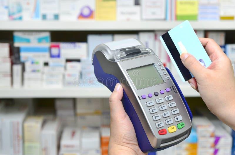 Klant die met een creditcard in apotheekdrogisterij betalen stock afbeeldingen