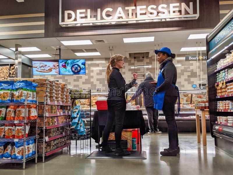 Klant die met een medewerker in de delicatessen in de kruidenierswinkel van Kirkland, bij de kaas en het vlees, spreekt stock afbeelding