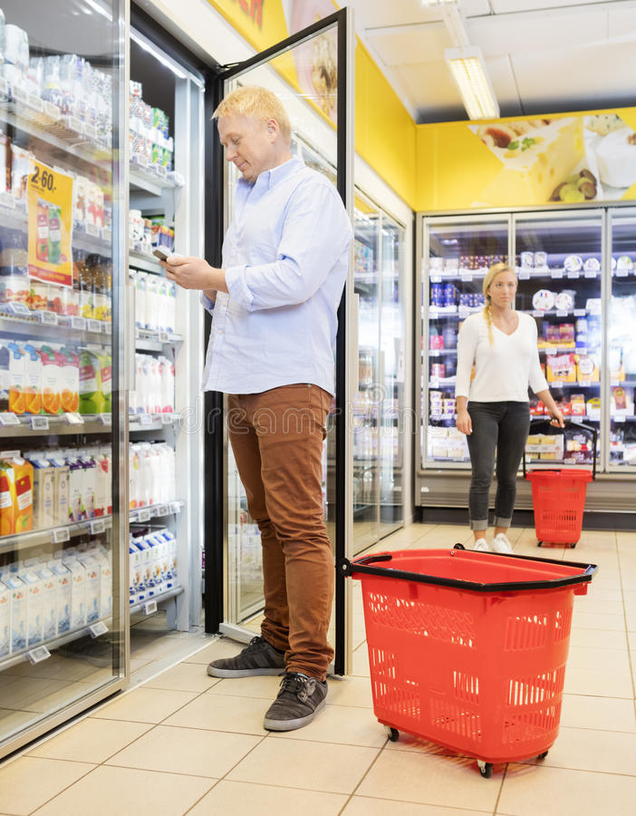 Klant die Mobiele Telefoon met behulp van bij Ijskast in Supermarkt stock foto