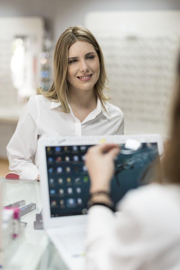 Klant die in optische apotheek op haar oogglazen wachten royalty-vrije stock fotografie