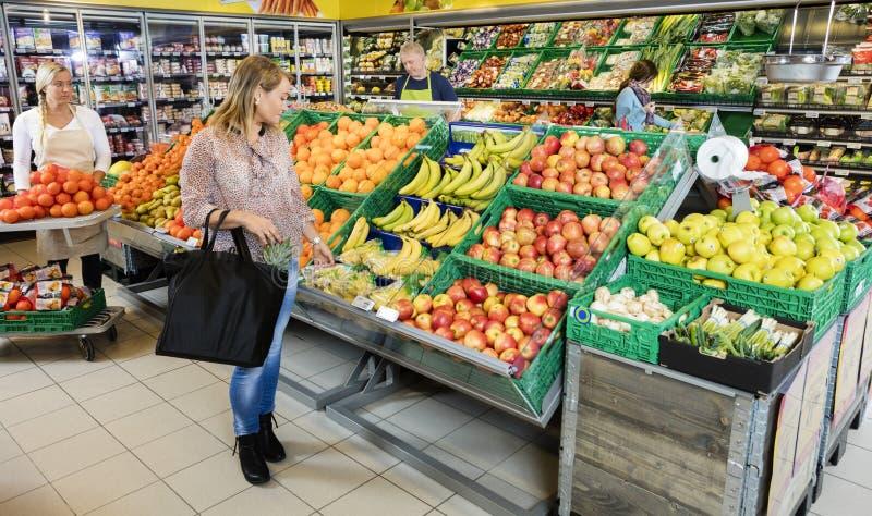 Klant die Vruchten in Kruidenierswinkelwinkel kiezen royalty-vrije stock foto's