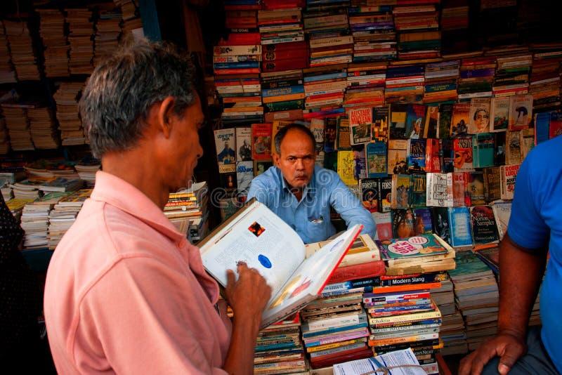 Klant en boekhandelaar op de Aziatische straatmarkt stock afbeeldingen