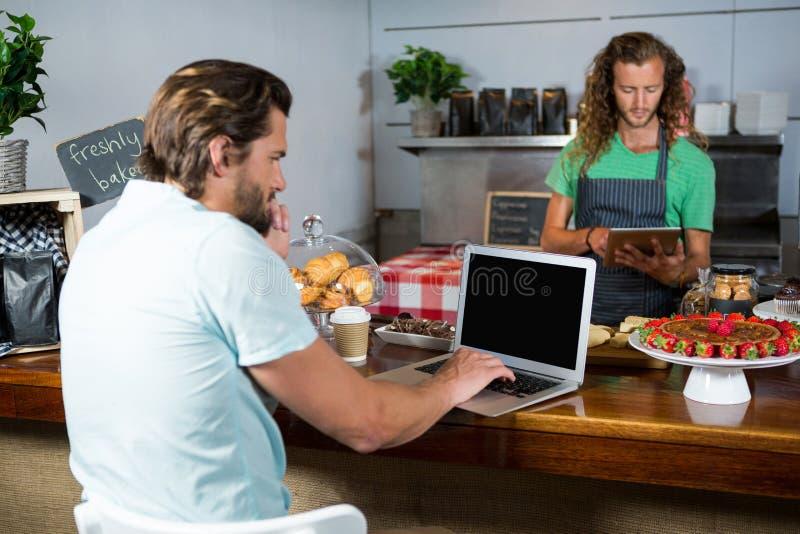 Klant en personeel die laptop en digitale tablet gebruiken bij teller stock foto's
