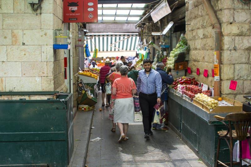 Klanten die door een smalle steeg in een bezige behandelde straatmarkt in Jeruzalem Israël dichtbij Jaffa-Straat overgaan stock fotografie