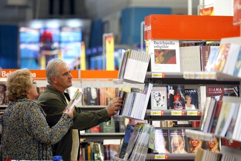 Klanten die voor boeken bij supermarkt winkelen stock afbeeldingen
