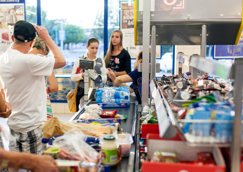 Klanten die voor het winkelen bij een supermarkt betalen royalty-vrije stock afbeelding
