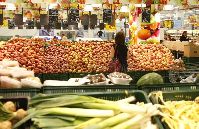 Klanten die voor kruidenierswinkels bij supermarkt winkelen royalty-vrije stock foto's