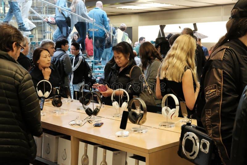 Klanten en het publiek in een bekende detailhandel wordt gezien, die hoofdtelefoons en andere verwante toebehoren proberen die royalty-vrije stock afbeelding