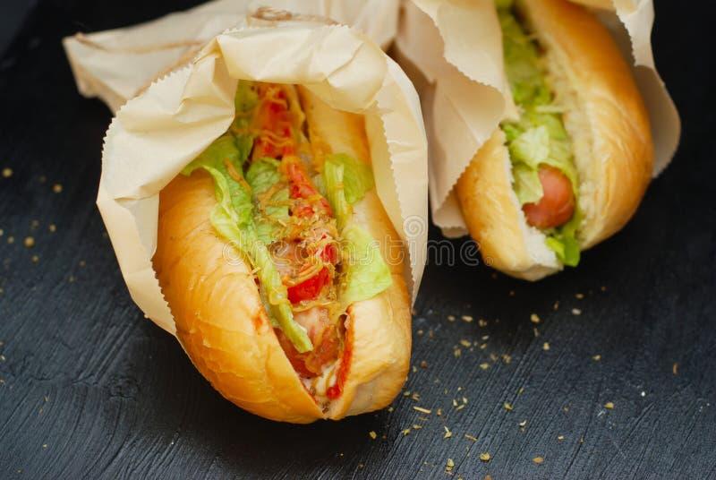 Klaphonden op Zwarte Raad Twee traditionele eigengemaakte hotdogs met verse groenten met Kruiden stock afbeelding