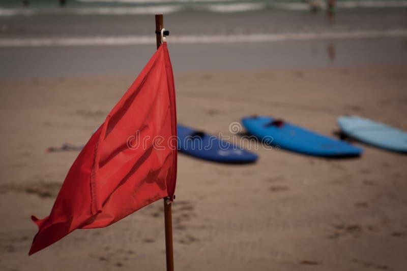 Klappe der roten Fahne auf dem Strand lizenzfreie stockbilder