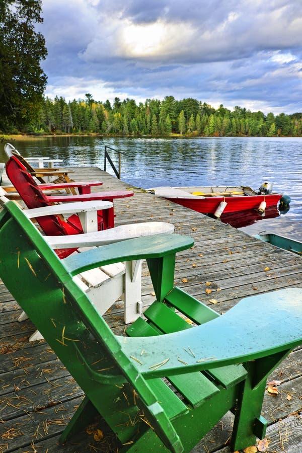 Klappstühle auf Dock in See stockbild