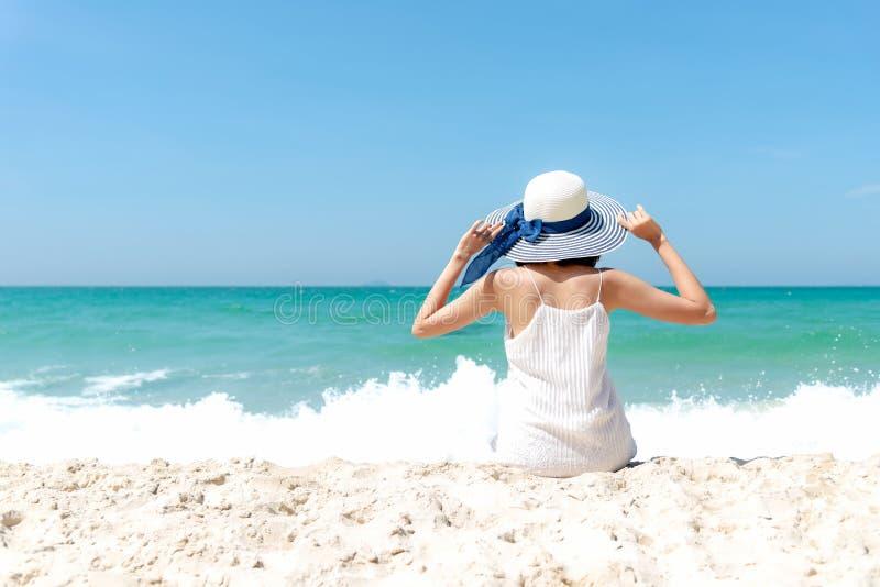 Klappstuhl auf Strand in Brighton Mode-Sommerreisen der Lebensstilfrau weißes Kleidertragende, die auf dem sandigen Ozeanstrand s lizenzfreie stockfotografie
