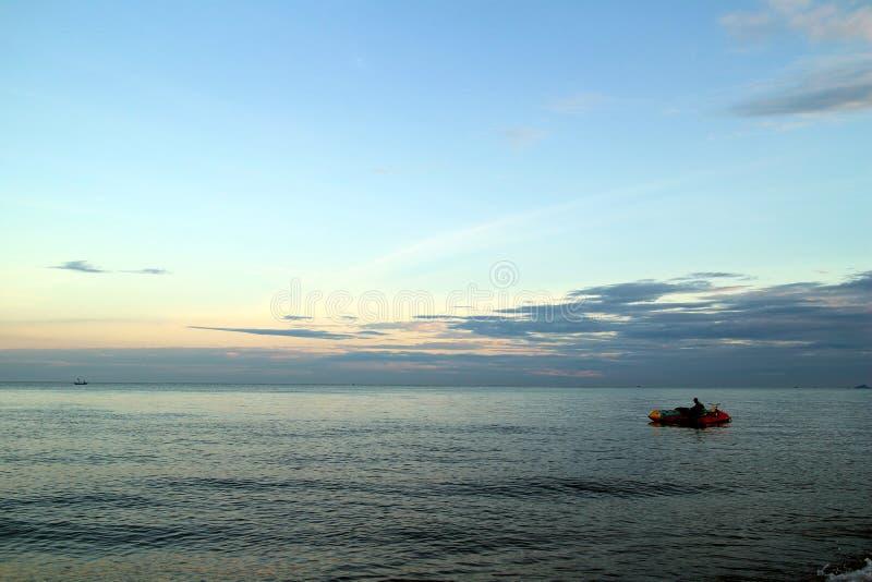 Klar blå himmel, blått hav, moln, solnedgång, bananfartyg royaltyfri bild