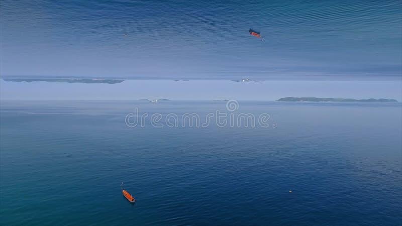 Klar bl? havsyttersida med krusningar och det ensamma r?da fartyget, spegelhorisonteffekt medel H?rligt lugna vatten av havet arkivbild