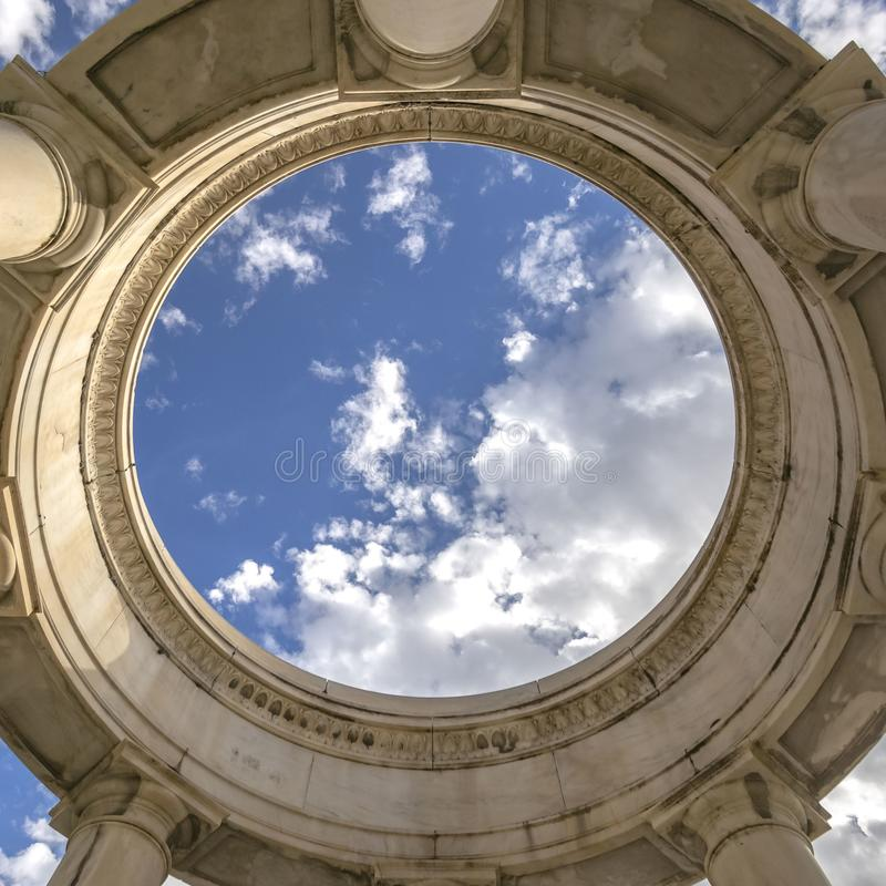 Klar fyrkantig rund struktur som stöttas av enorma kolonner som beskådas på en solig dag royaltyfri fotografi