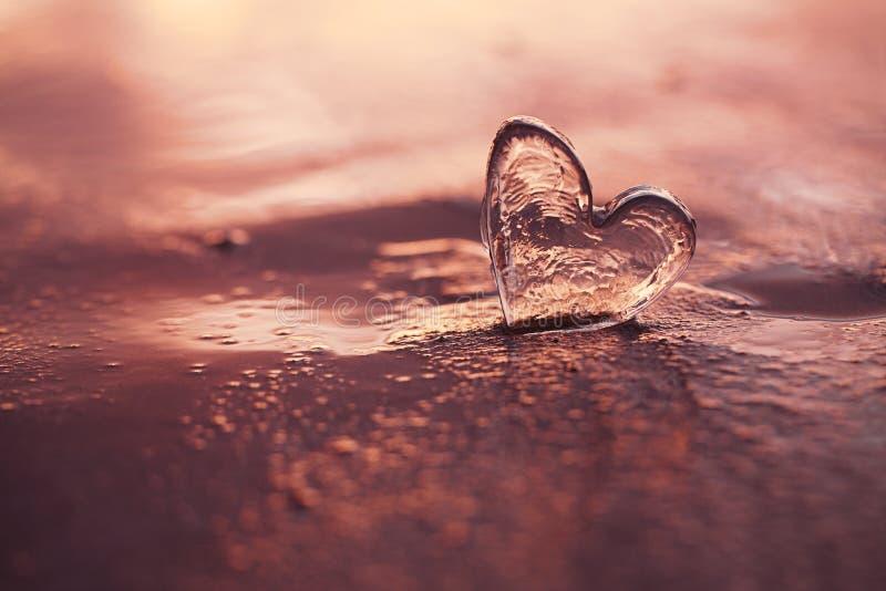 Klar glass hjärta på sandstranden med soluppgångsolljus arkivfoton