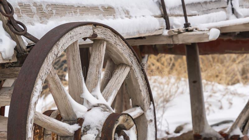 Klar panorama en gammal trävagn med rostiga hjul som dammas av med insnöad vinter arkivfoton