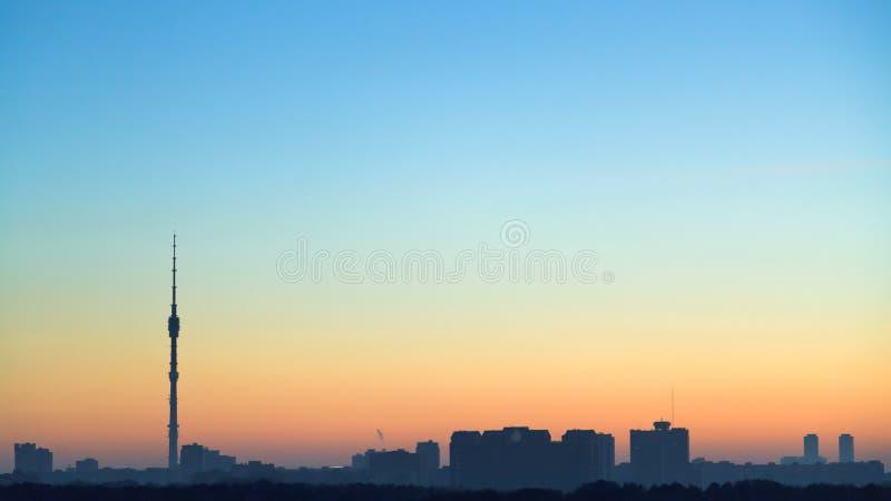 Klara blått och guling som gryr himmel över stad royaltyfri foto