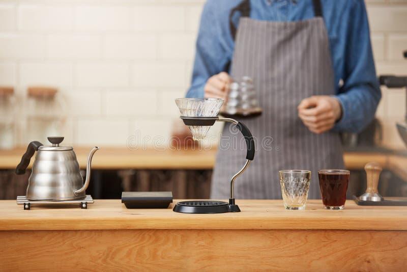 Klara Coffes s Barista förberett kaffe med den manuella droppandebryggaren royaltyfria foton