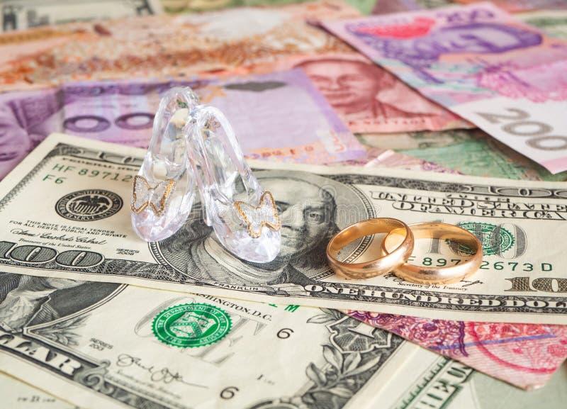 Klara exponeringsglaspar av skor och vigselringar på olika valutor Pengar f?r f?r?lskelse royaltyfria bilder