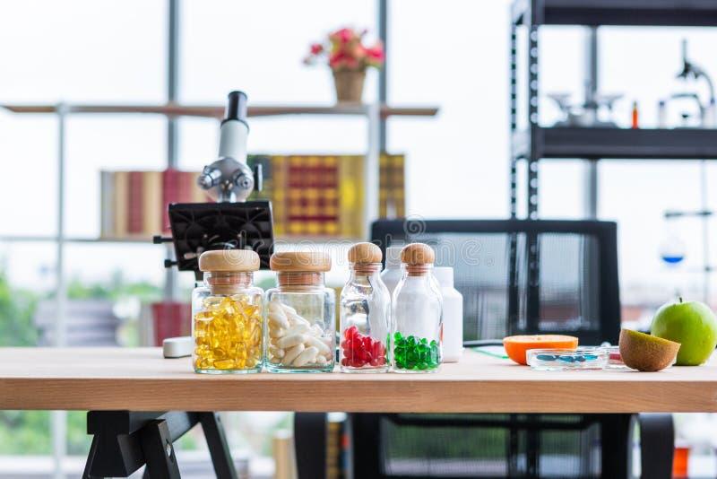 Klara glasflaskor av färgrika mjuka tillägg för mat för gelatinkapsel på näringsfysiologdoktorstabellen i laboratoriumrum royaltyfria bilder