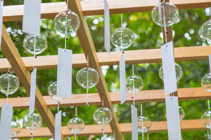 Klara glass vindchimes hänger från den wood strukturen under vindChi royaltyfri fotografi