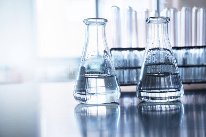 Klare Flasche zwei mit Wasser vor Reagenzglas im Ausbildungschemie-Wissenschaftslaborhintergrund lizenzfreies stockbild