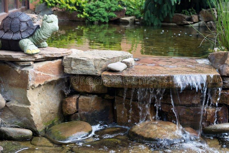 Klare Wasserströme über den Steinen im Yard Künstlicher Teich unter den Bäumen Lanshafta-Entwurf lizenzfreie stockfotografie
