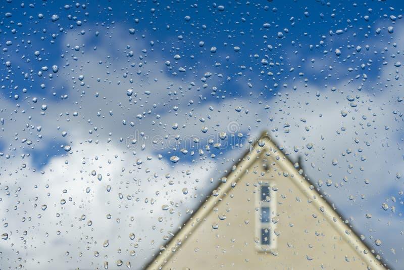 Klare Wassertropfen auf sauberem Fensterglas mit einem Haus des Hintergrundes stockfoto