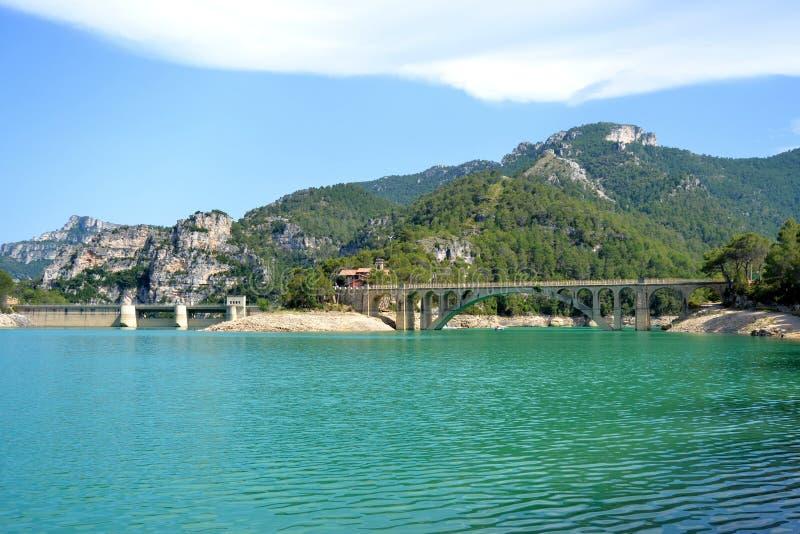 Klarer blauer See mit Brücke und Bergen stockbild