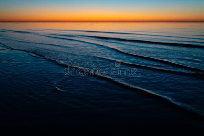Klarer erstaunlicher Sonnenuntergang in den baltischen Staaten - Dämmerung im Meer mit Horizont belichtet durch die Sonne stockbild