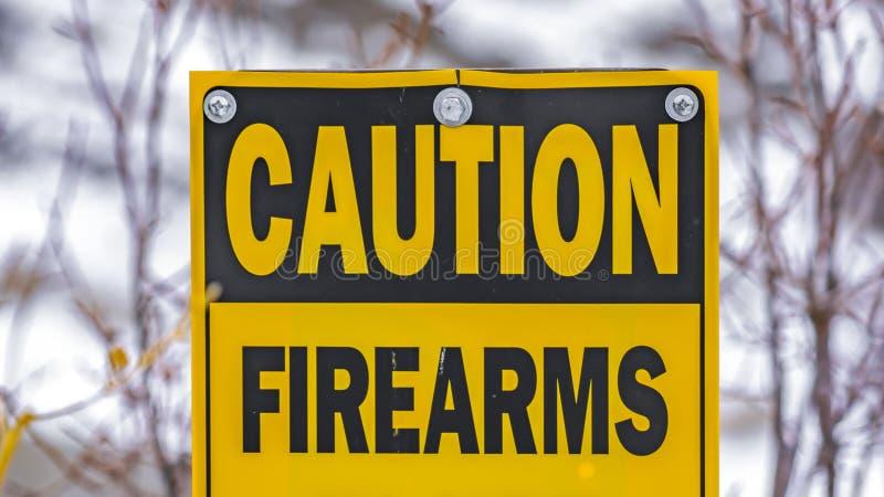 Klarer Panorama-Abschluss oben eines gelben Zeichens, das liest, die gebräuchlichen Vorsicht-Feuerwaffen halten ab stockfotografie