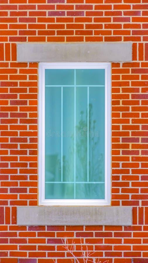 Klarer vertikaler Abschluss oben des rechteckigen Fensters eines Gebäudes mit Wand des roten Backsteins lizenzfreie stockfotografie