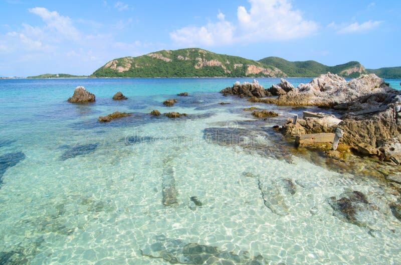 Klares blaues Meerwasser mit Stein- und großem Berg. lizenzfreies stockbild