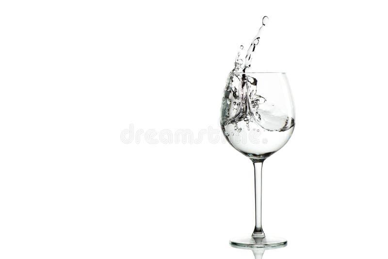 Klares Wasser, das im Weinglas spritzt stockbild