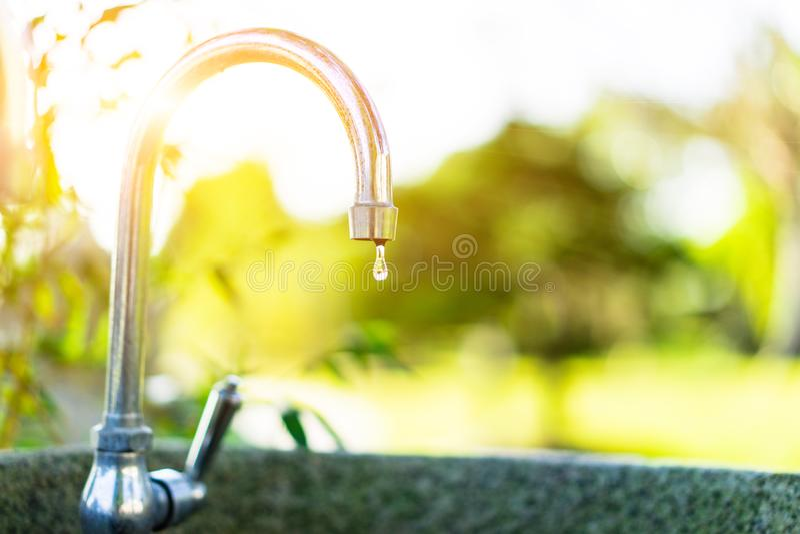 Klares Wasser vom Hahn im hellen Morgengarten stockbild