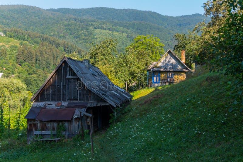 Klargöras gamla stall för en by nära huset på lutningarna av berget av solen royaltyfri bild